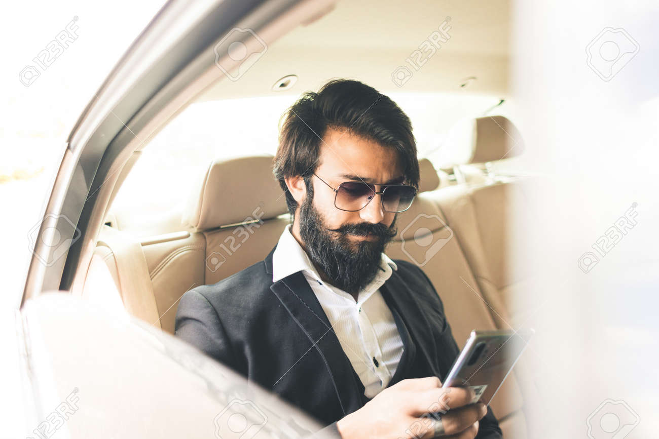 Stylish handsome Hindu businessman works in the backseat of the car and uses the phone. Safe and comfortable luxury travel - 171704367