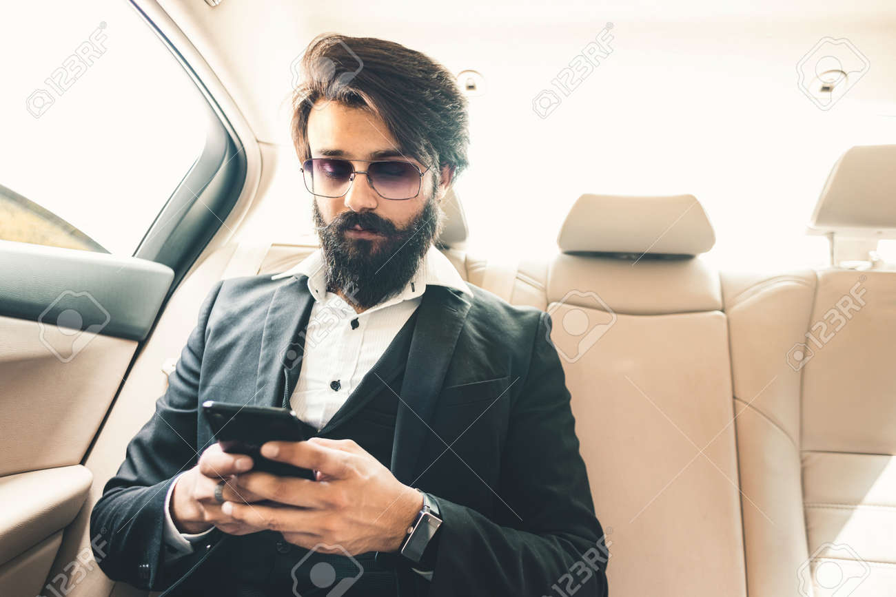 Stylish handsome Hindu boss with glasses and a beard works with the phone in the back seat of the car. Safe and comfortable business travel - 171617339