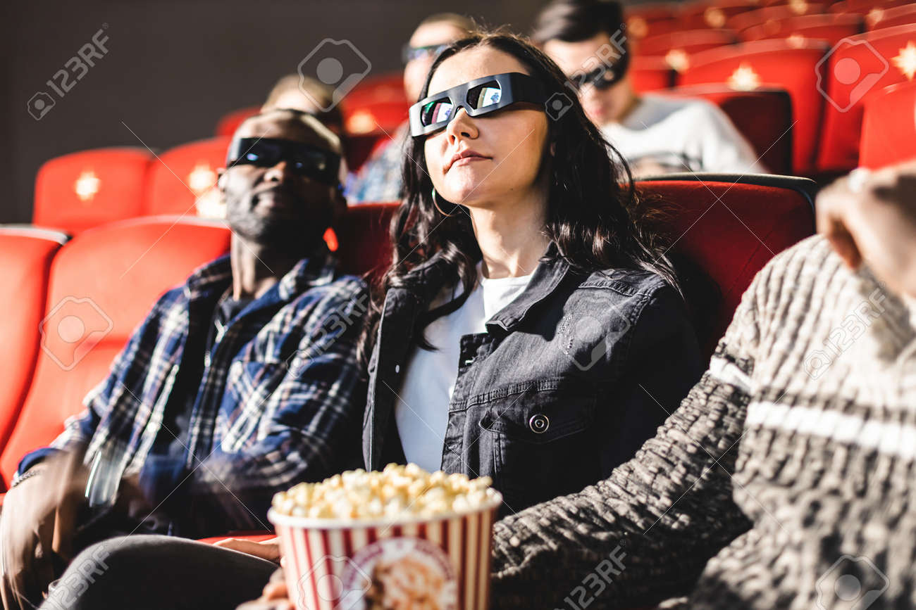 Friends are watching a movie in the cinema. People sit in the armchairs of the cinema and look at the screen with special glasses for 3D - 171660199