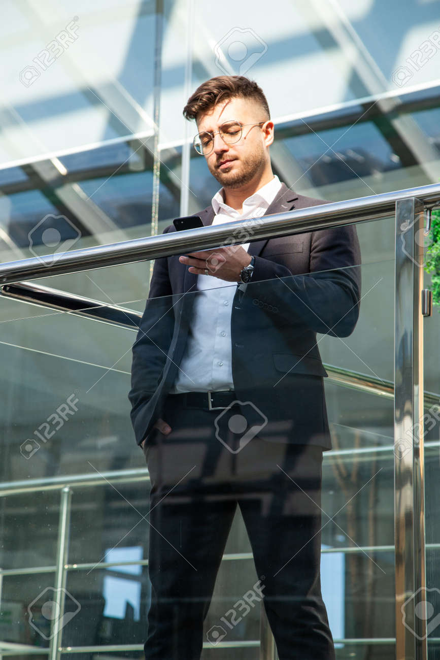Portrait of a businessman in suit are standing on the background of glass offices. - 171660357