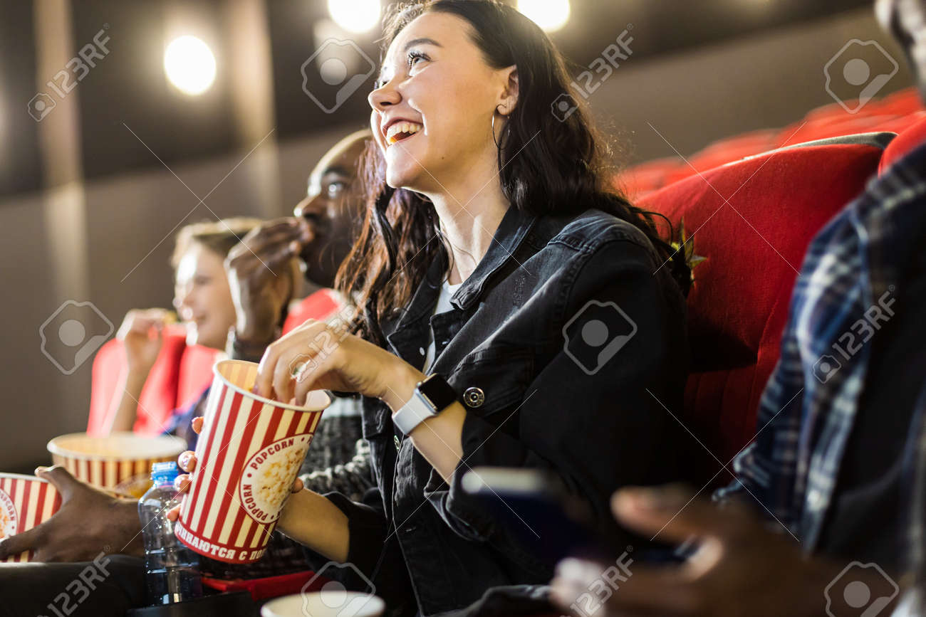 Friends are watching a movie in the cinema with popcorn. People sit in the armchairs of the cinema and look at the screen - 171660405