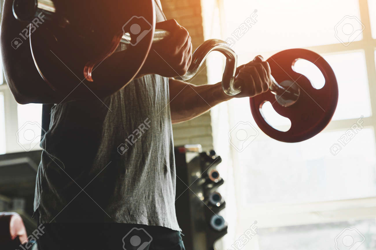 Silhouette photo of a muscular young athlete doing exercises with a barbell in the gym. Power training close up - 171978608