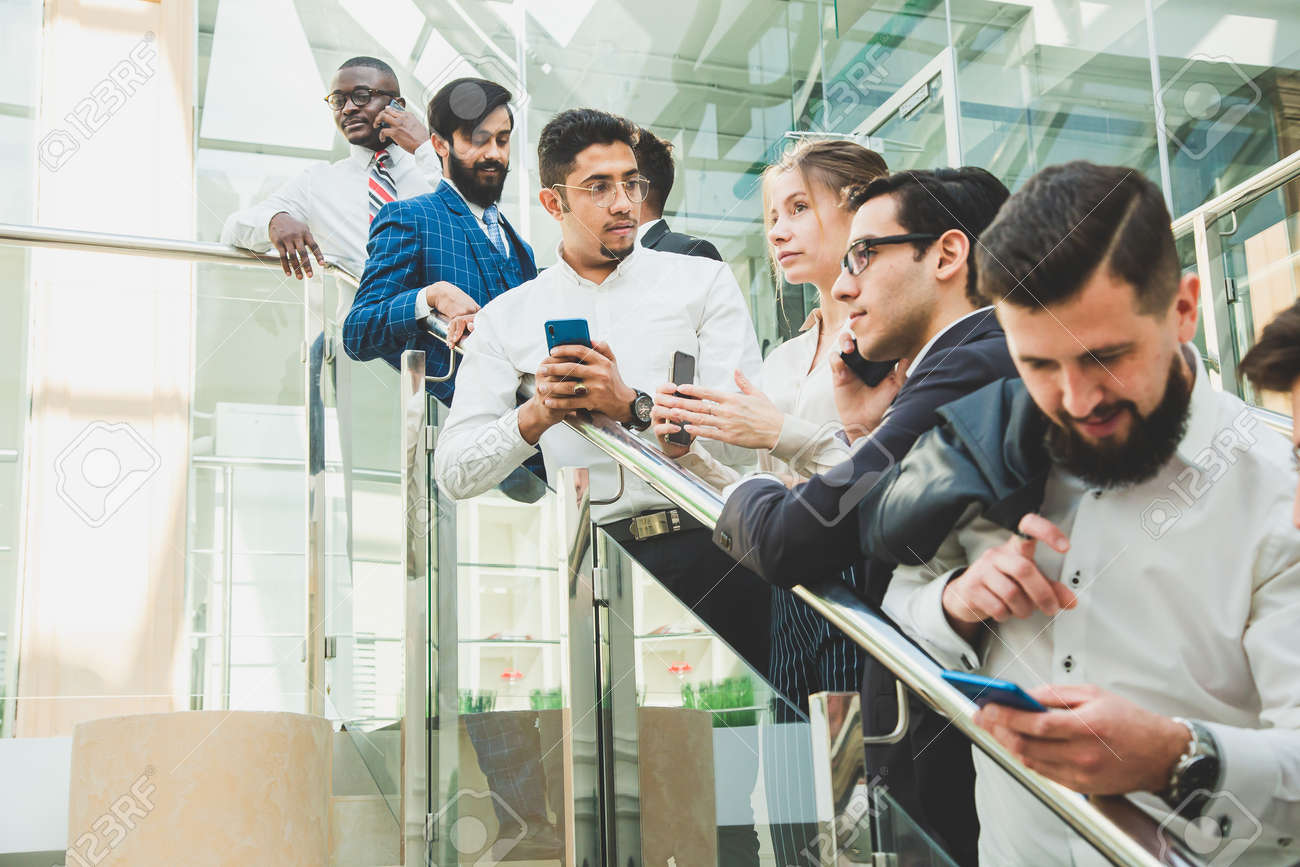 young business people arego down the stairs and talking on the background of glass offices. Corporate businessteam and manager in a meeting. - 171899851