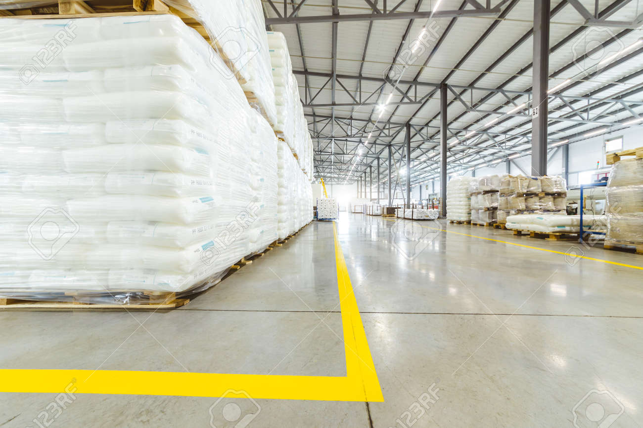 Spacious light interior of a large warehouse in a factory with special racks and shelves and products placed on them. - 171899890