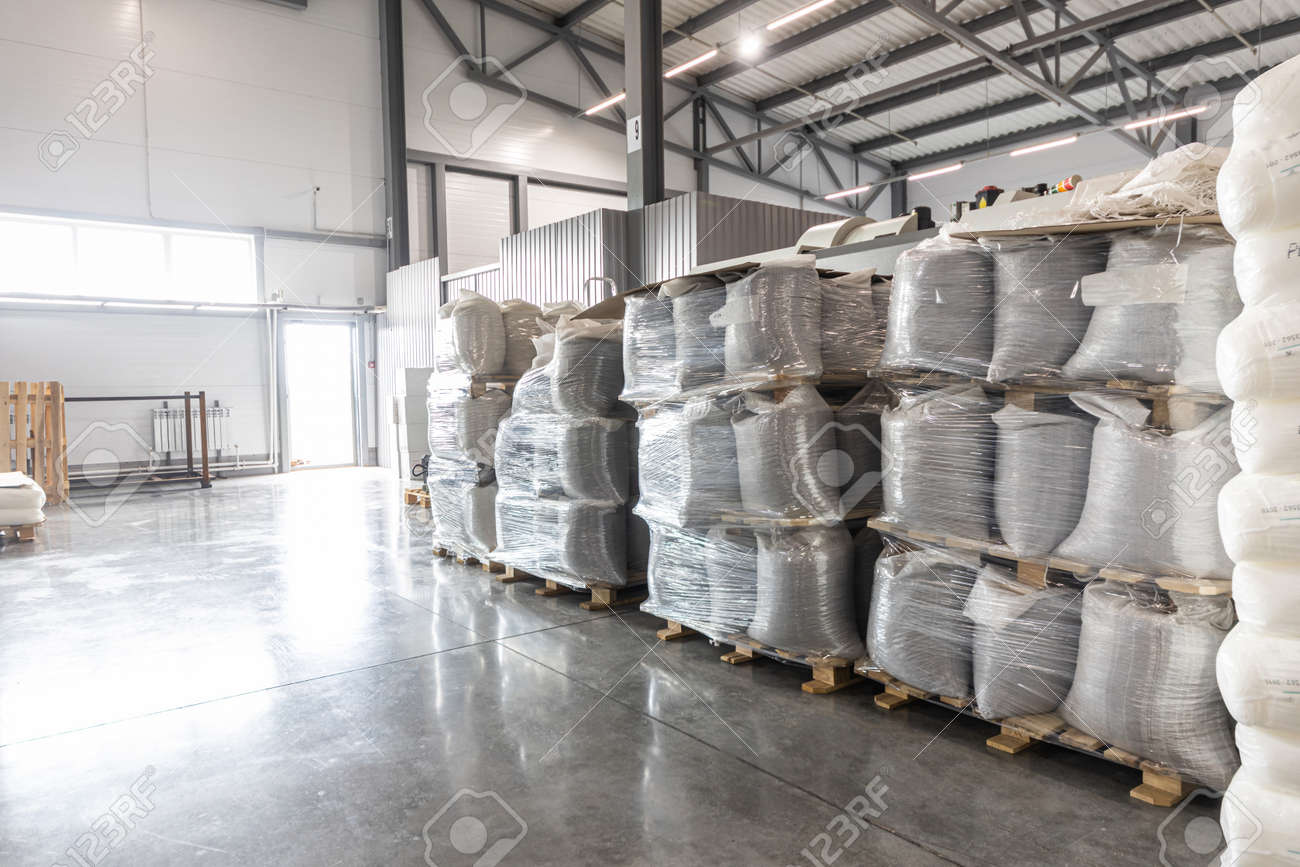 Spacious warehouse in a factory with special racks and shelves and products placed on them. - 171900114