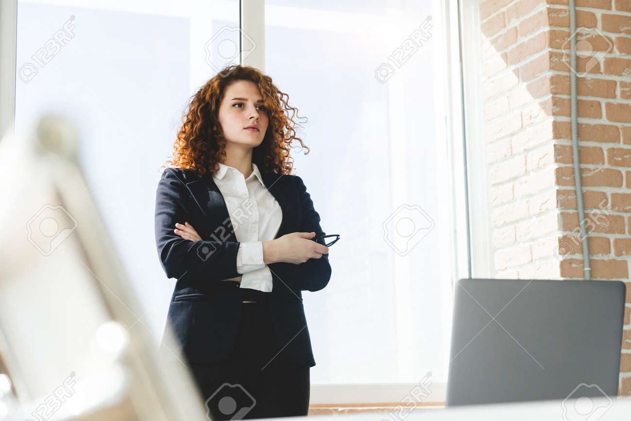 Portrait of a beautiful successful young business woman with red curly hair in the office interior stands near the window - 171943482