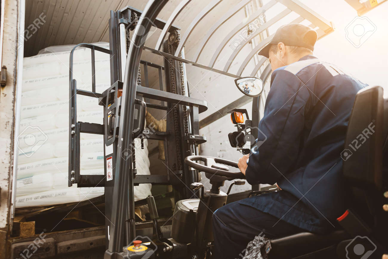 A man on a forklift works in a large warehouse, unloads bags of raw materials - 171983157