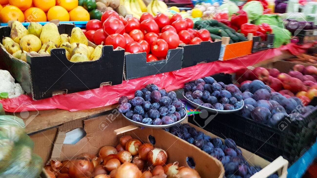 A variety of vegetables and fruits lying on a market counter for sale by a customer. Trade in agricultural products. Nitrates and pesticides. Genetically modified food. Farm fruits. Fiber and vitamins. - 131367425