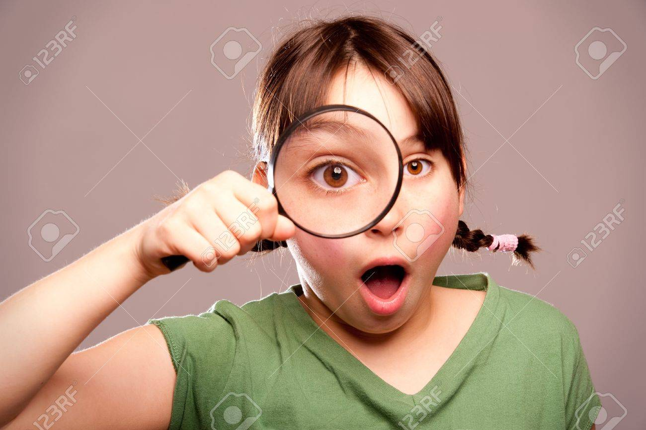 little girl looking at camera through magnifying glass Stock Photo - 17606108