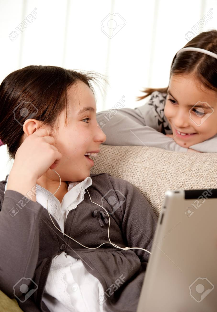 two girls on sofa with touch tablet computer Stock Photo - 17606112