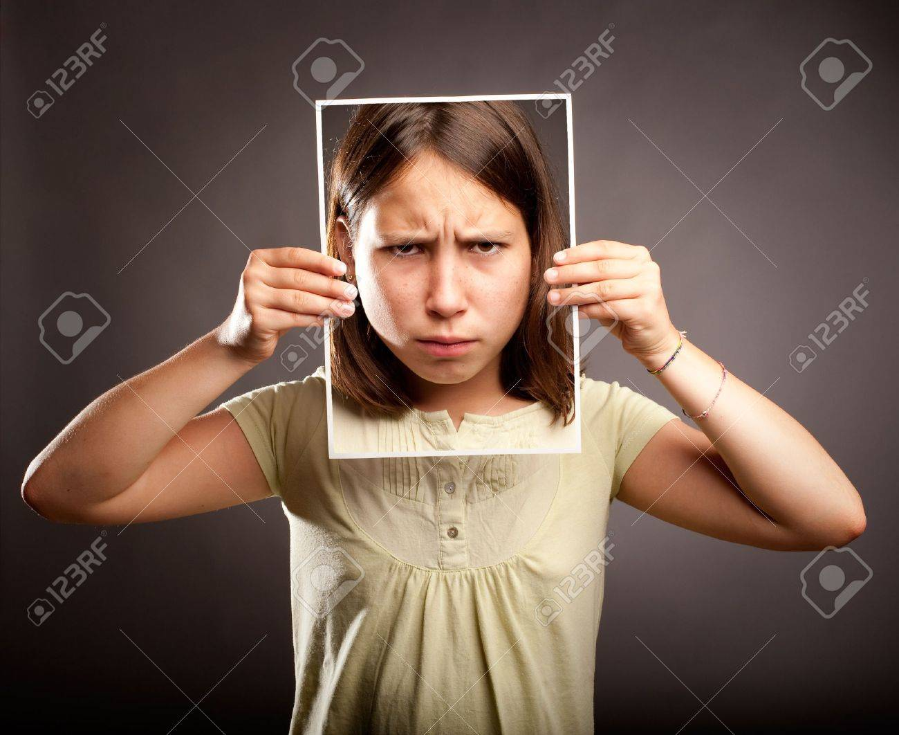portrait of young girl holding a photography of herself with sad expression Stock Photo - 21626618