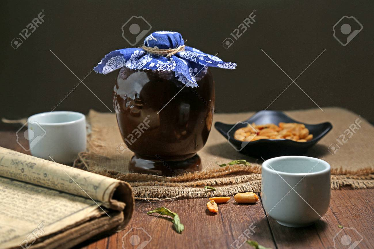 Ceramic bottle glass book placed on a wooden table - 53024246