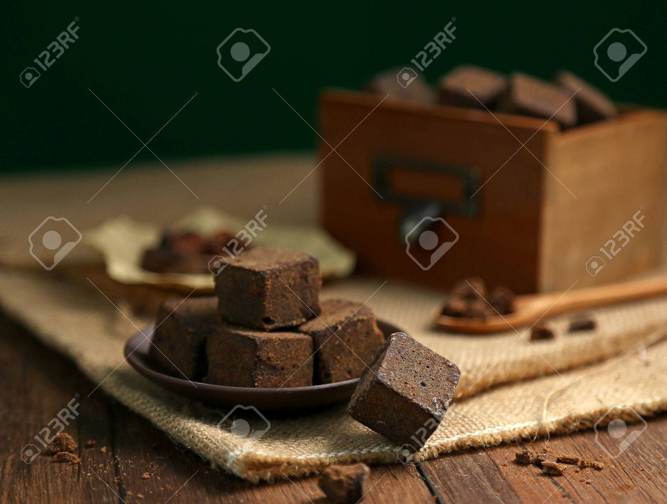 Brown sugar chunks in wooden boxes and plates - 53973789