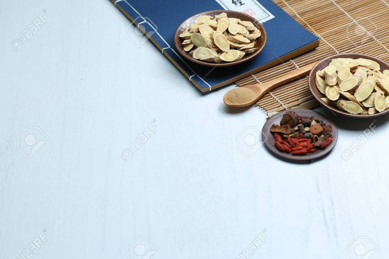 Traditional Chinese medicine and ancient medical book on white desk - 65948243