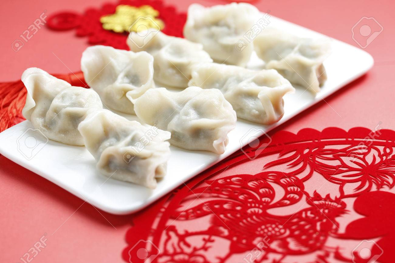 Spring Festival - dumplings and paper-cut on red background - 66845553