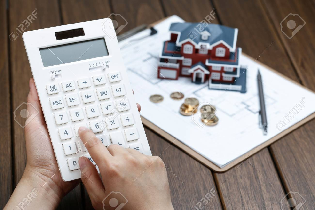 A female hand operating a calculator in front of a Villa house model - 72280886
