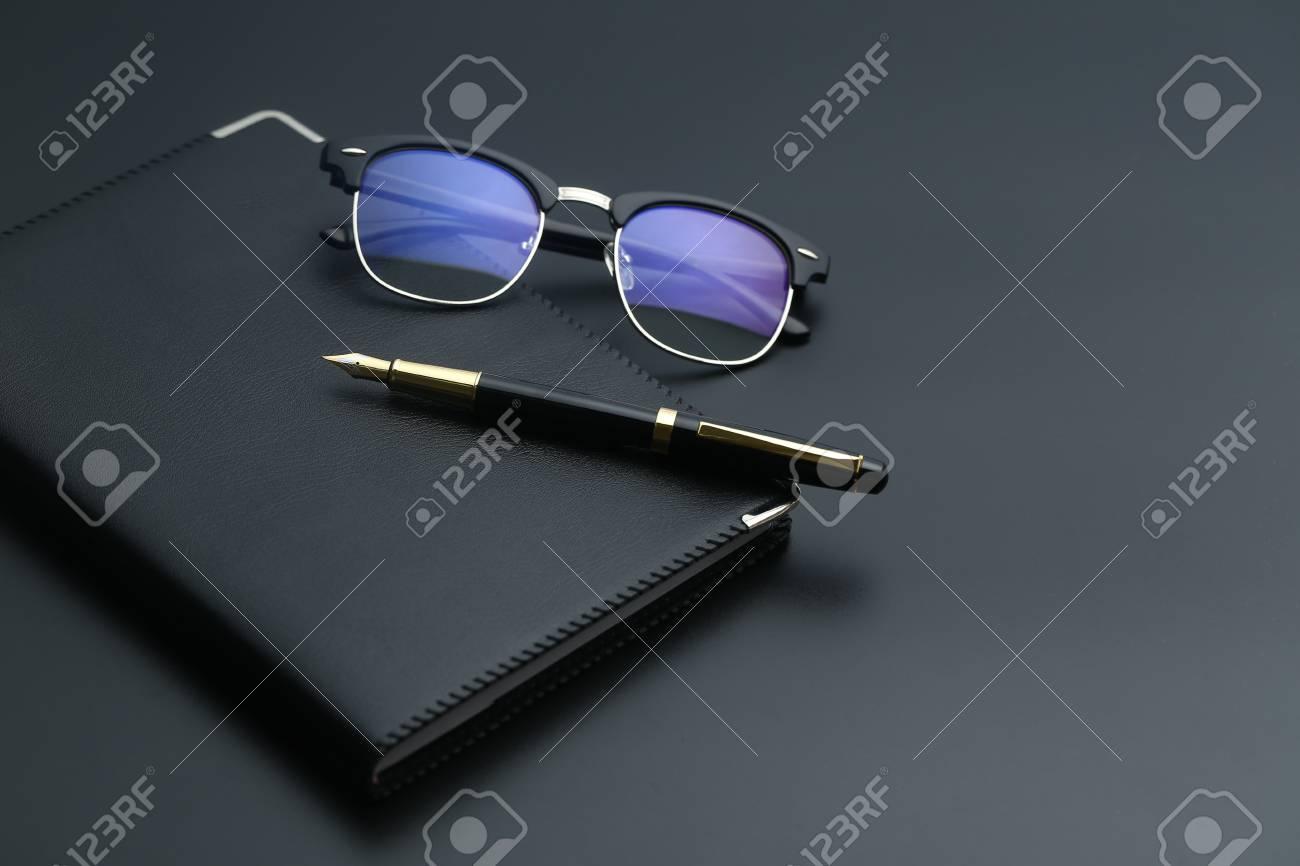 Stylo doré carnet calculatrice et lunettes sur un bureau noir