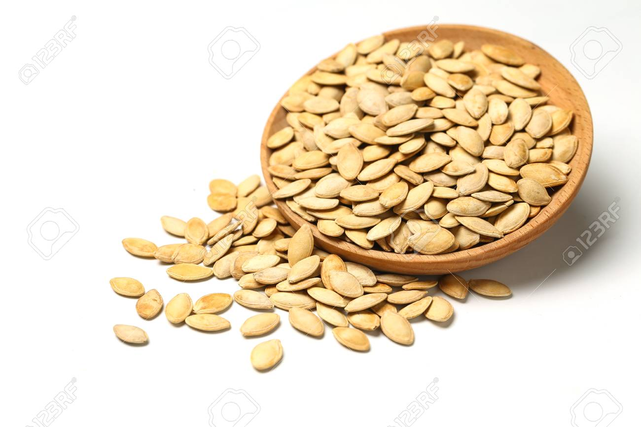 pumpkin seeds in wooden plate isolated on white background - 90369720