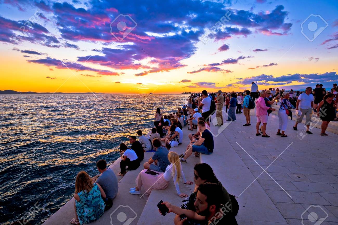 ZADAR, CROATIA - July 18 2017: Unidentified people on Zadar sea organs at sunset. Many tourists visits unique architectural object located on Zadar waterfront - musical instrument powered by the sea streams. - 95345654