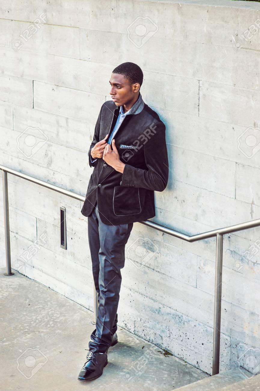 superior quality united states famous brand Jeune homme afro-américain vêtu d'une veste à la mode noire, pantalons,  chaussures en cuir, debout contre le mur dans la rue à New York, les mains  sur ...