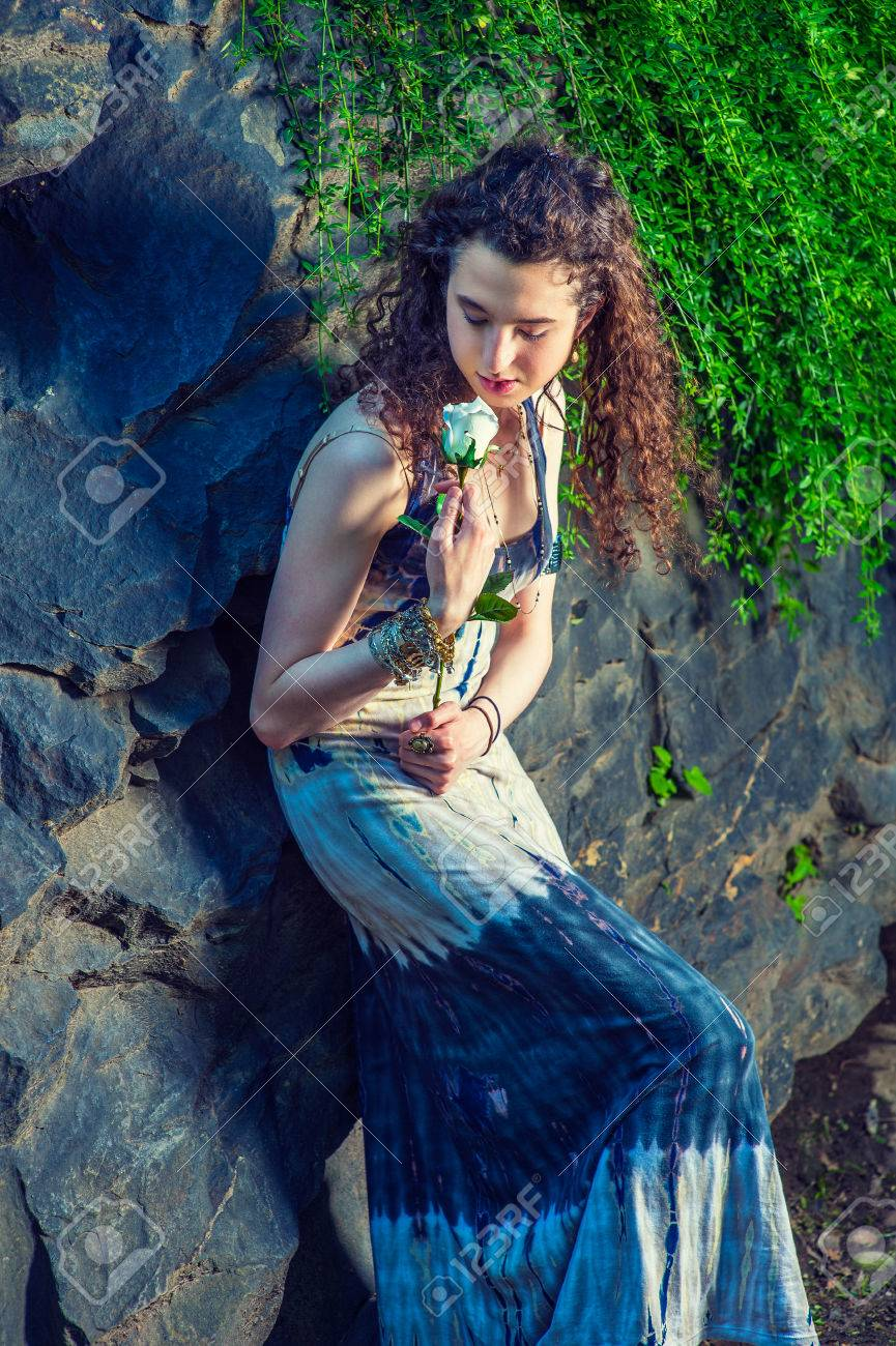 575453f119a American teenage girl with long curly hair talking to flower, wearing  patterned long dress,