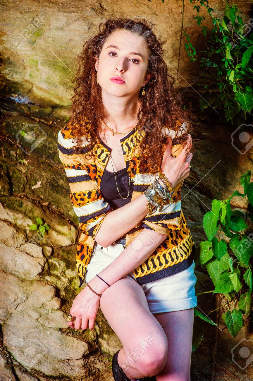 522a01969e4 Stock Photo - Young Woman Casual Fashion. American Teenage Girl with curly  long hair wearing patterned fashion jacket, short pants, chunky chain  bracelet, ...