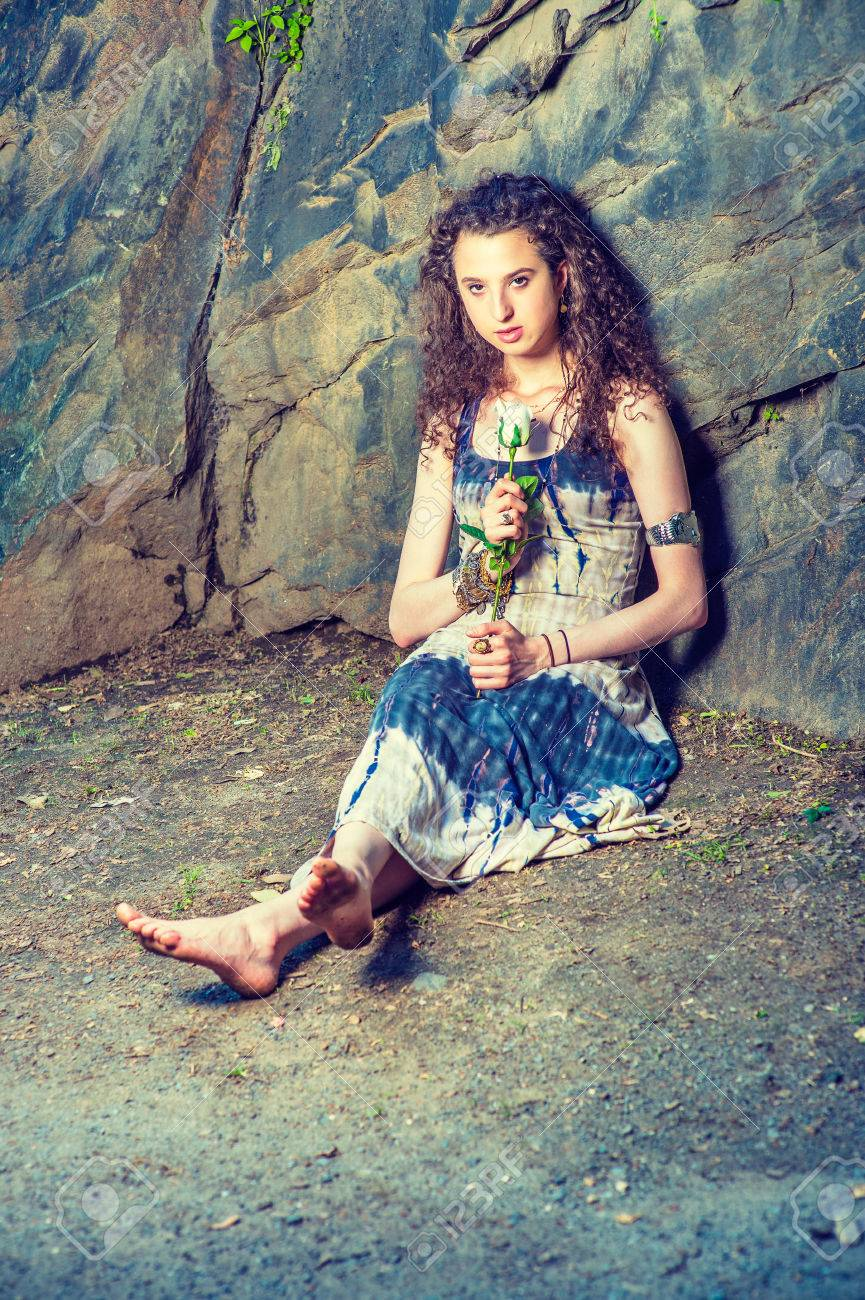 7d418a4694a Stock Photo - Waiting for You. American teenage girl with curly long hair wearing  patterned long dress, bracelet, barefoot, sitting on ground against rocky  ...