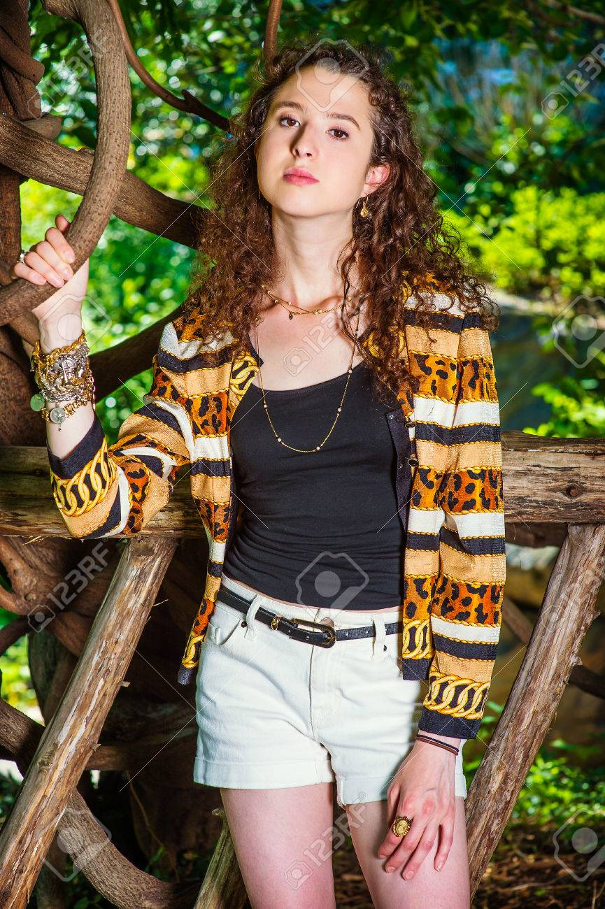 cb3a08d27e3 American teenage girl with curly long hair, wearing patterned fashion  jacket, black undershirt,