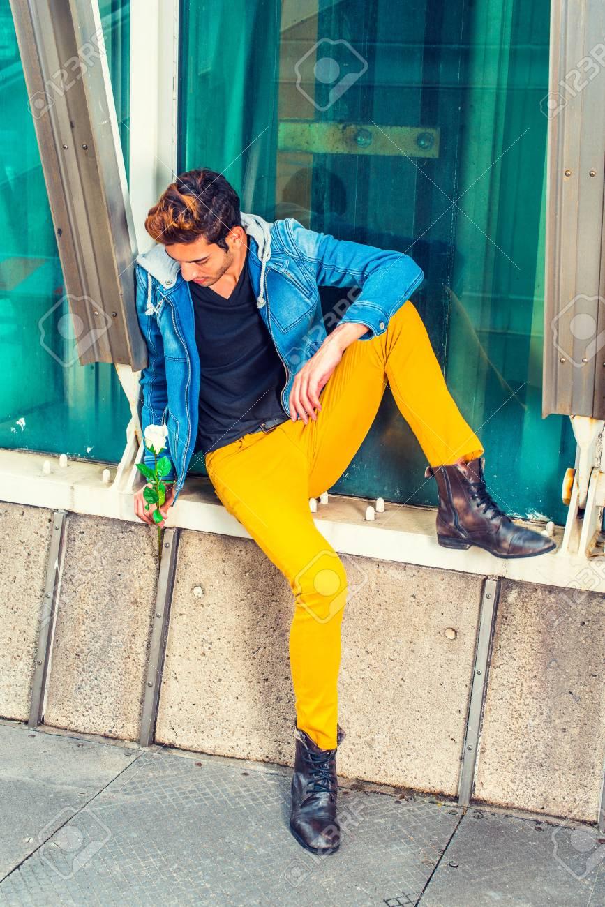 Tu Me Manques Vêtu Dune Veste Bleue à Capuche Pantalon Jaune Chaussures De Botte En Cuir Un Beau Jeune Homme Est Assis Près Dune Structure