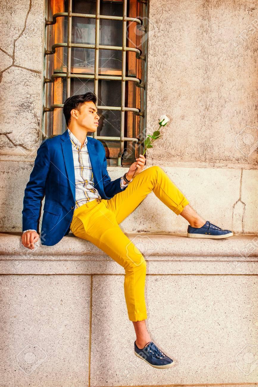 official photos 79d4e ac4f5 Man Miss You. Vestirsi in giacca blu, pantaloni gialli, scarpe da  ginnastica casual, un giovane bello è seduto vicino a una finestra in  strada, a ...