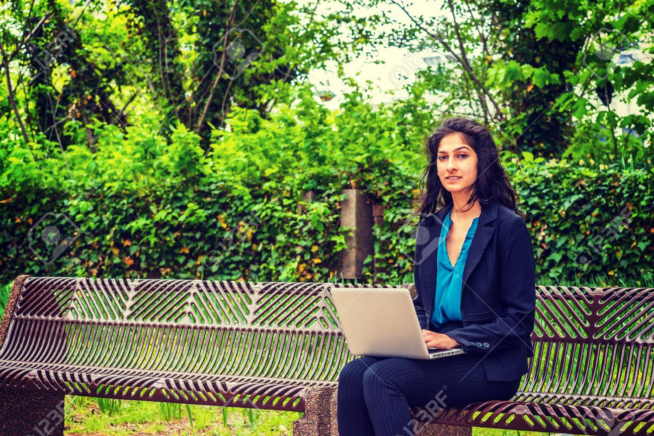 East Indian American college student studying in New York, sitting on  chairs on green campus, reading, working on laptop computer  Concept of