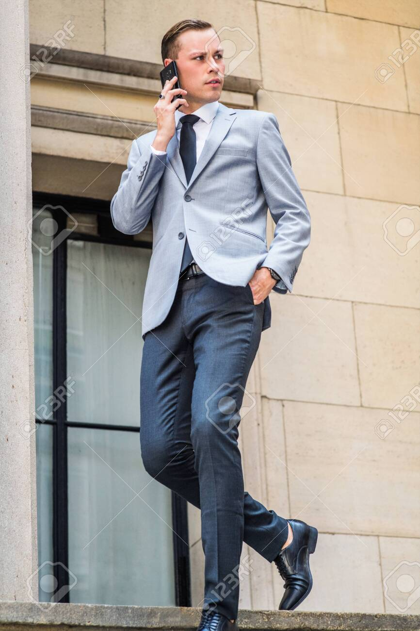 Young Businessman Street Fashion in New York City. Man wearing gray blazer, white shirt, black tie, pants, leather shoes, walking down stairs by window outside office building, talking on cell phone. - 125497717