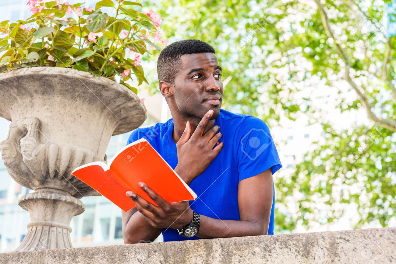 Young African American College Student studying in New York, wearing blue short sleeve T shirt, standing, back bending forward on top of wall on campus, holding red book, hand touching thin, thinking. - 159270945