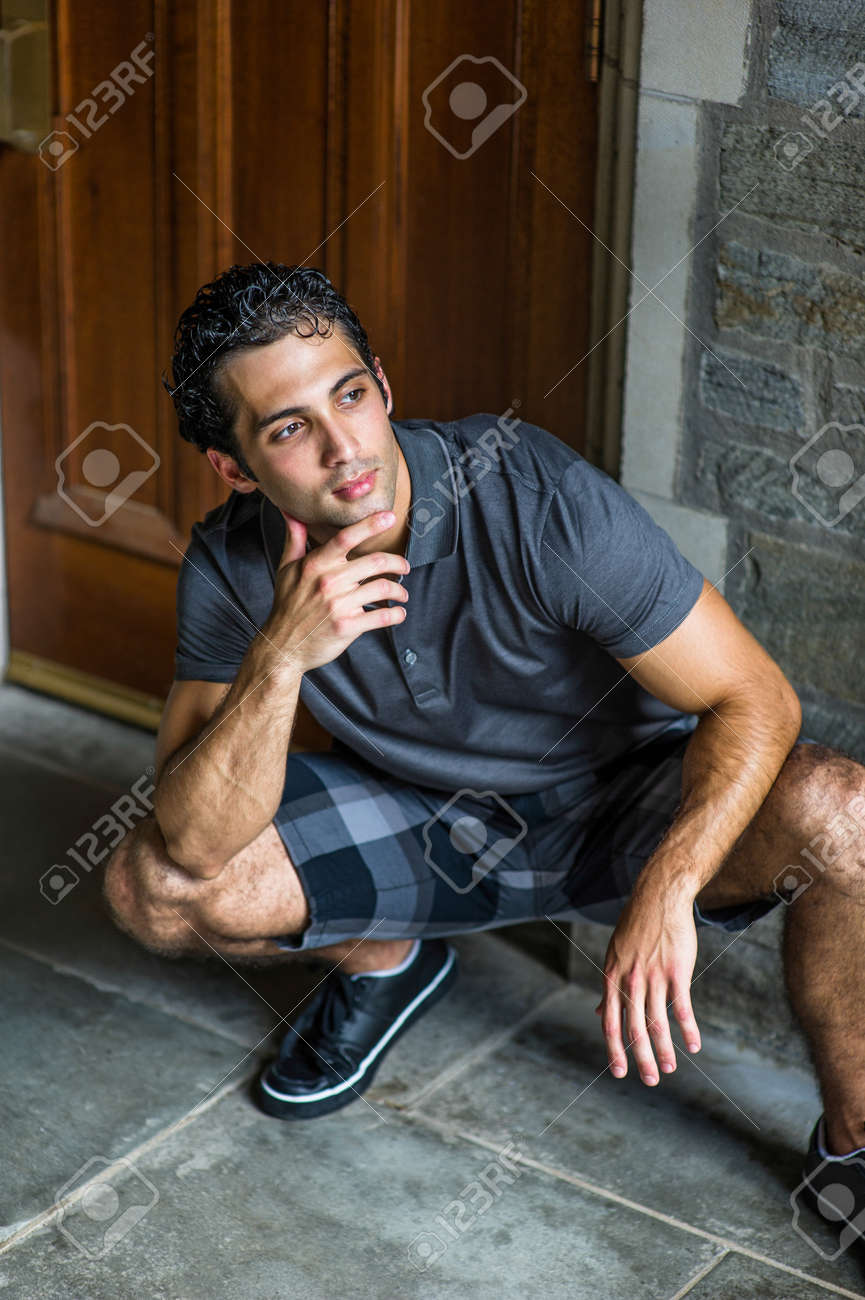 Dressing in a gray polo shirt, pattern shorts and black leather sneakers, one hand touching his chin, a young strong handsome guy is squatting in the front of the door, relaxing and thinking. - 170751271