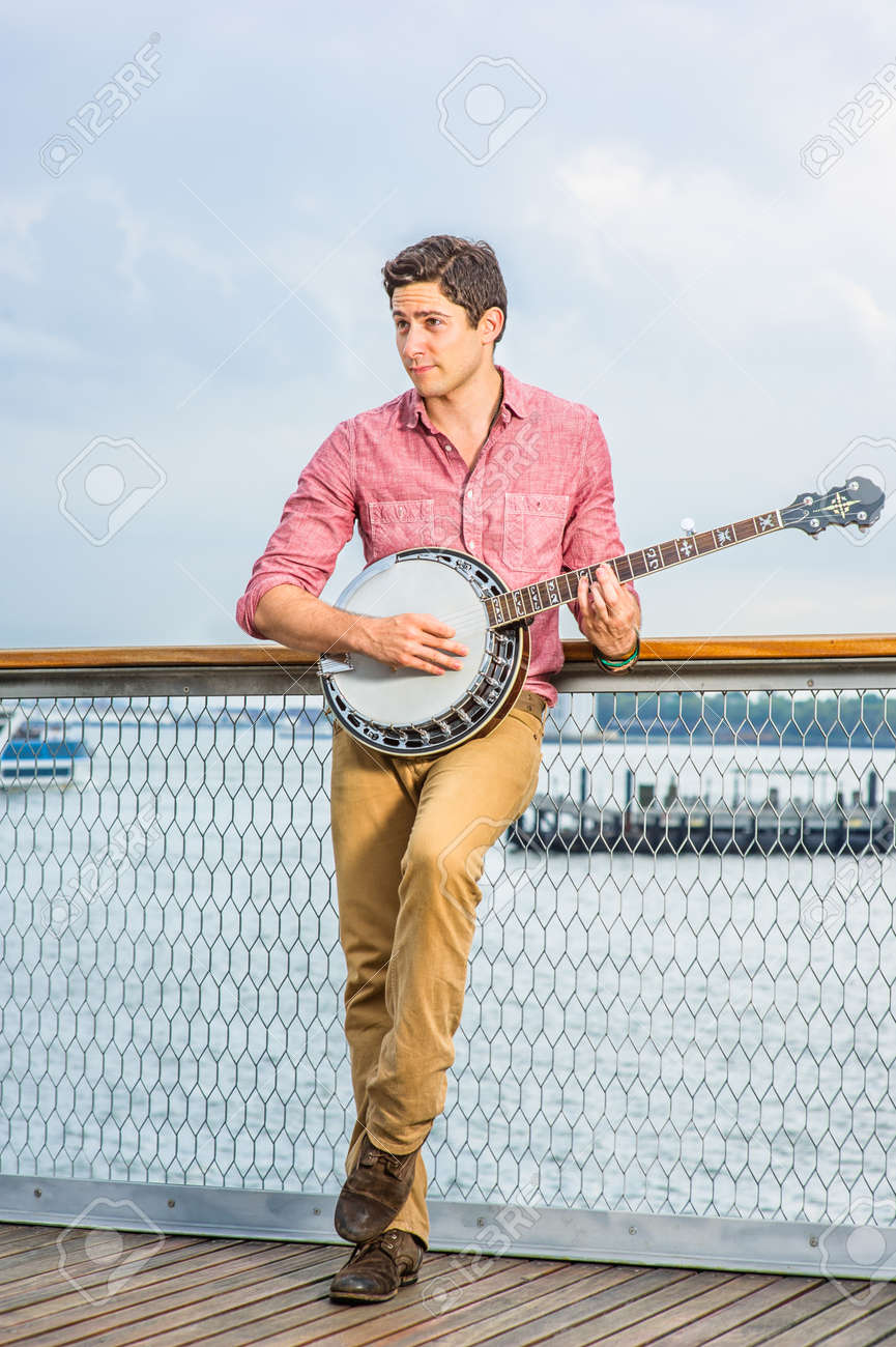 Dressing in light red shirt, dark yellow trousers and brown shoes, looking faraway and stepping his foot, a young musician is playing a banjo on the deck - 171462622