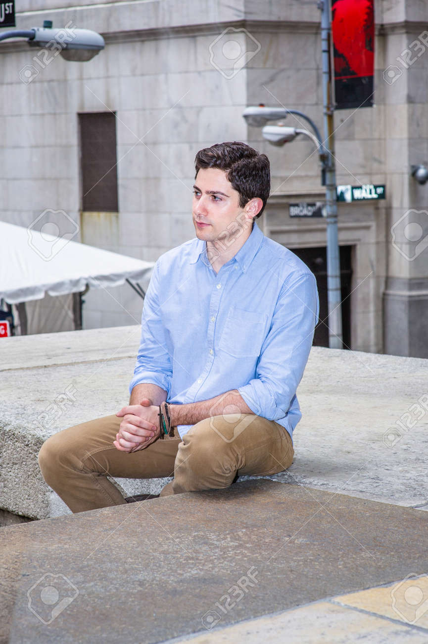 Clamping his hands and looking forward, a young handsome guy is sitting on a stage in the corner of the street, relaxing and thinking. - 171462631