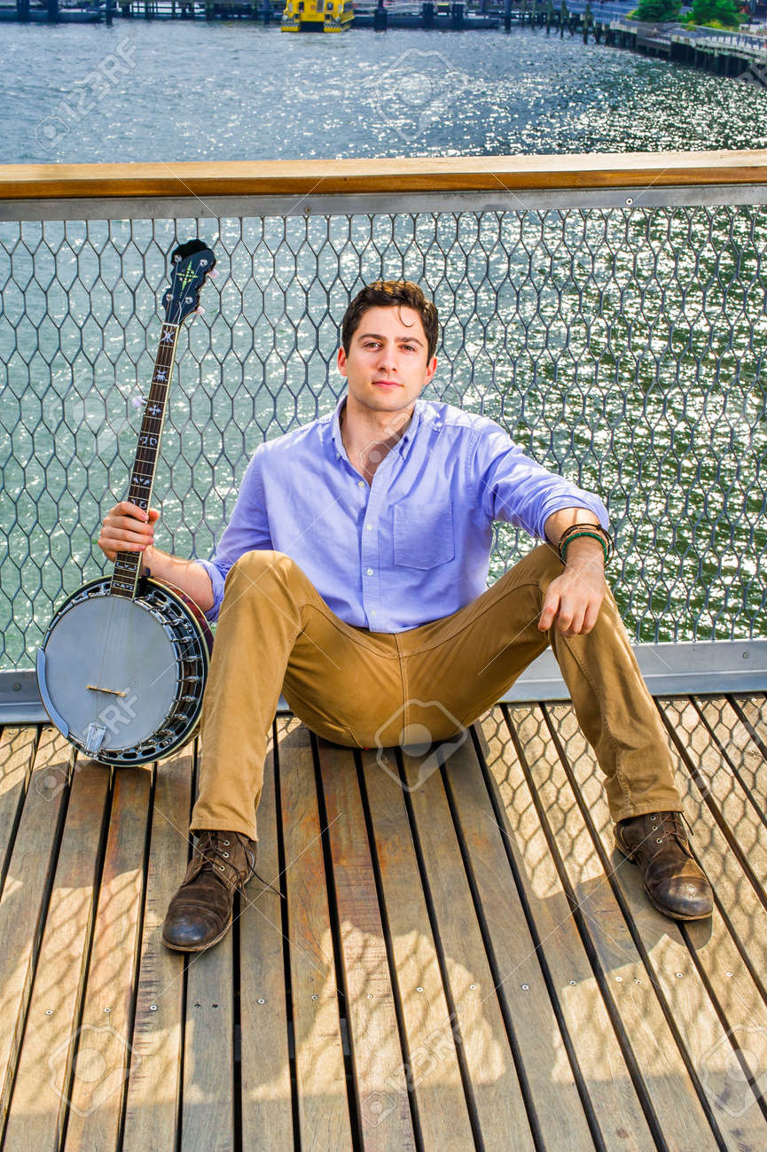 Dressing in a light blue shirt, dark yellow jeans and brown boot shoes, holding a banjo, a young musician is sitting on the deck against a fence, relaxing - 171462664
