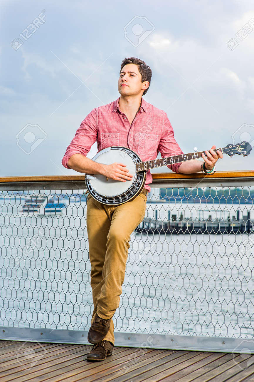 Dressing in light red shirt, dark yellow trousers and brown shoes, looking up and stepping his foot, a young musician is playing a banjo on the deck - 171462667