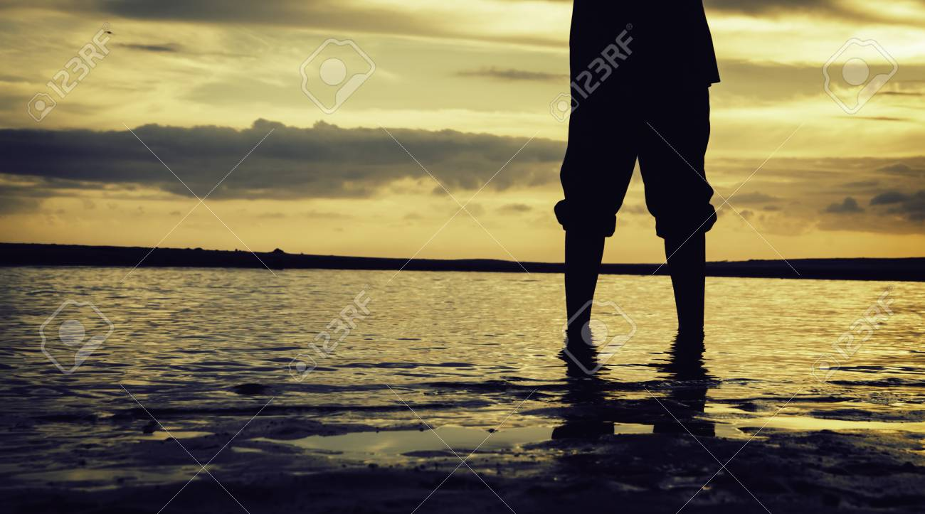 Silhouette and cropped image concept lonely boy standing at sandy beach with beautiful sunrise sunset background