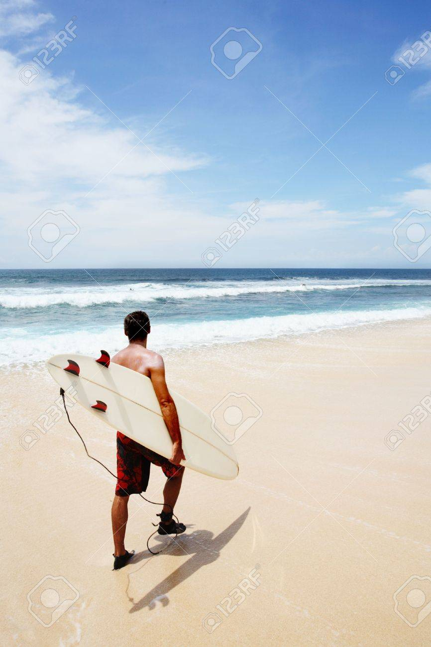 Young man going to surf at Dreamland, Bali Stock Photo - 289577