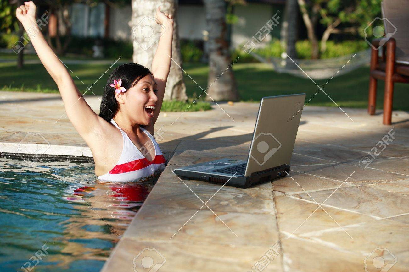 Woman in a swimming pool surpised when looking at her laptop. Stock Photo - 648436