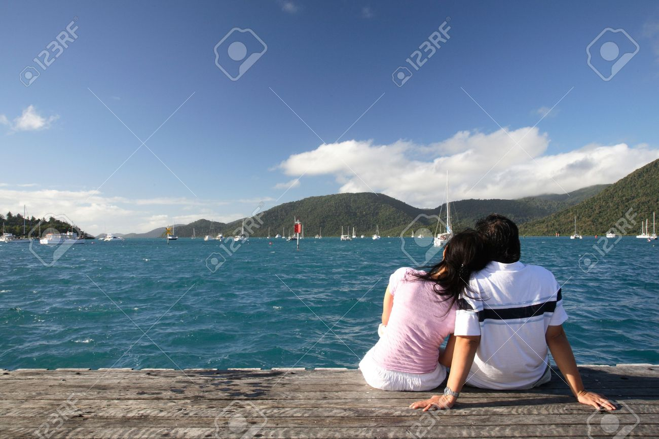 Asian couple enjoying the beautiful sea landscape while sitting on a piece of wood Stock Photo - 665281