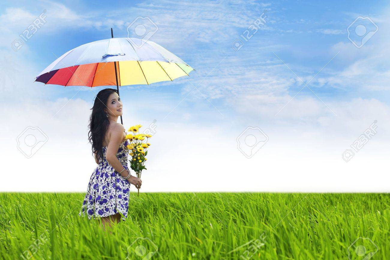 Sexy Asian woman carrying flowers shot in the middle of paddy field Stock Photo - 14683503