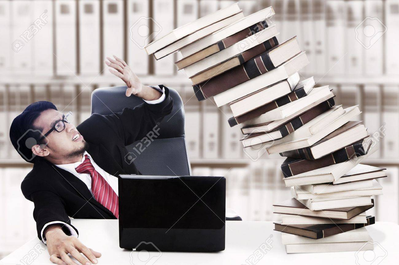 Scared businessman with stack of books which about to collapse. Shot in the office Stock Photo - 14683068