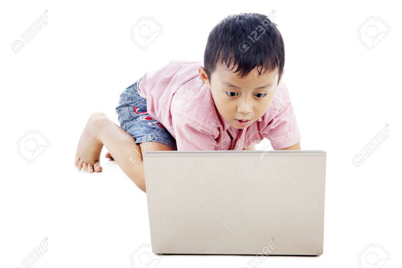Cute asian boy using laptop computer seriously. shot in studio Stock Photo - 14683042