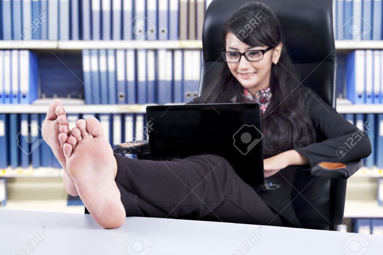 Successful Businesswoman using laptop with Feet Up on a Table, shot in the office Stock Photo - 14684437