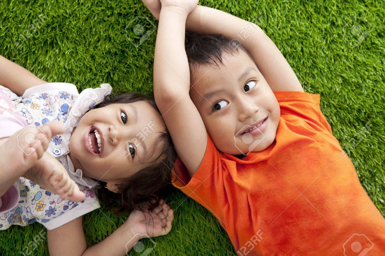 Cute happy asian siblings lying on the green grass shot at meadow Stock Photo - 14684175