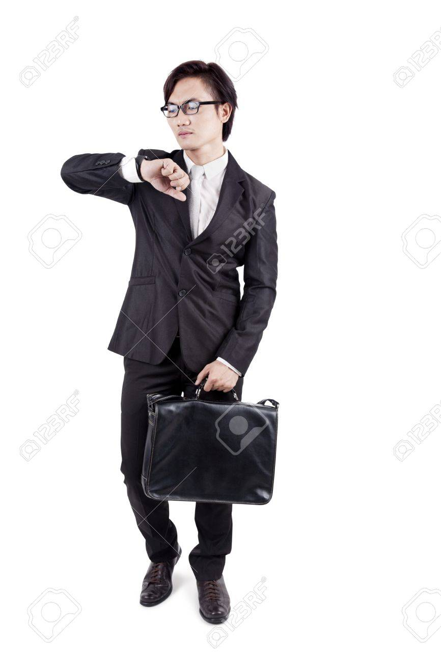 Late to work: Portrait of young business man carrying briefcase and checking the time. isolated on white Stock Photo - 14684330