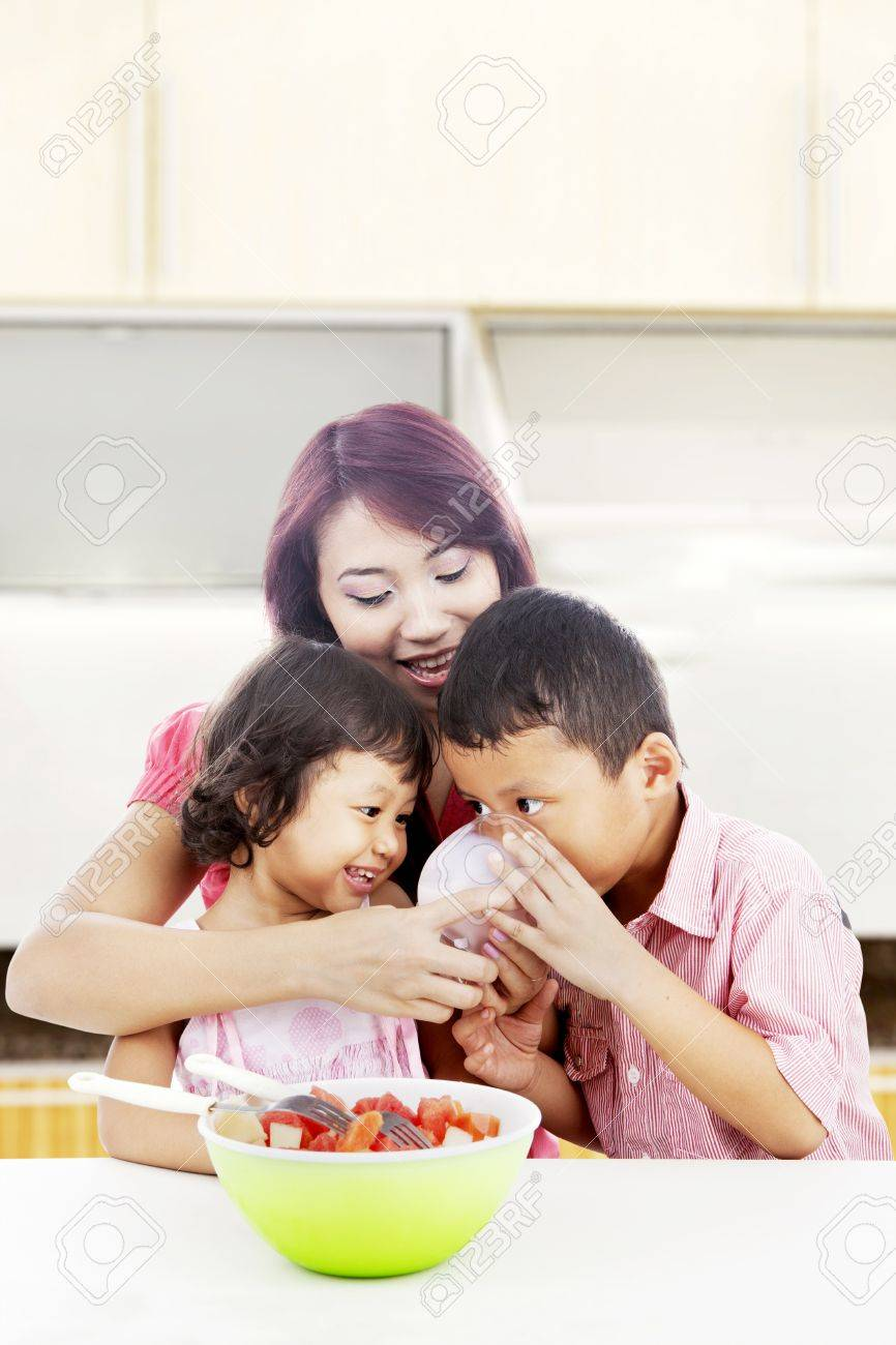 Young mother with her children in the kitchen and helping her son to drink Stock Photo - 14684374