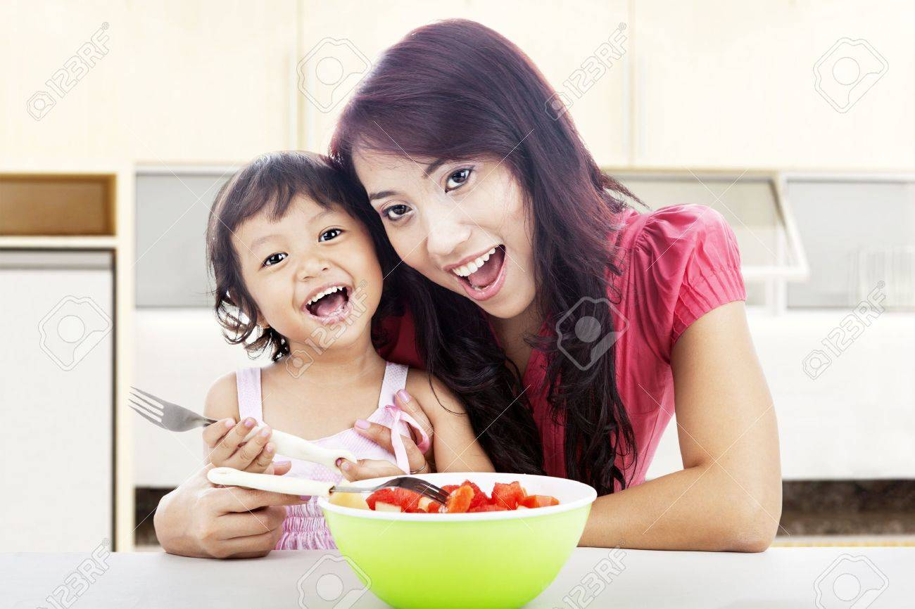 Smiling young asian mother and her daughter with fruit salad. shot in the kitchen Stock Photo - 14779123
